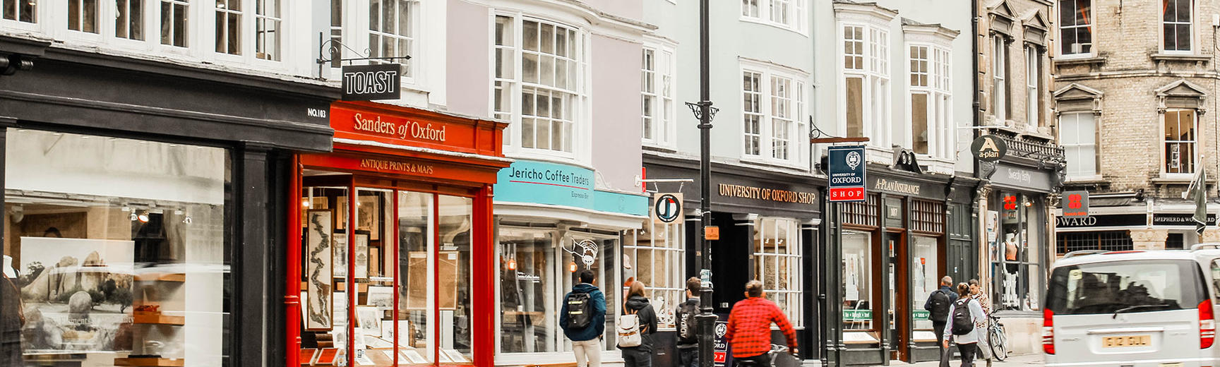 Image of Oxford city street including shops, cyclist, cars and pedestrians