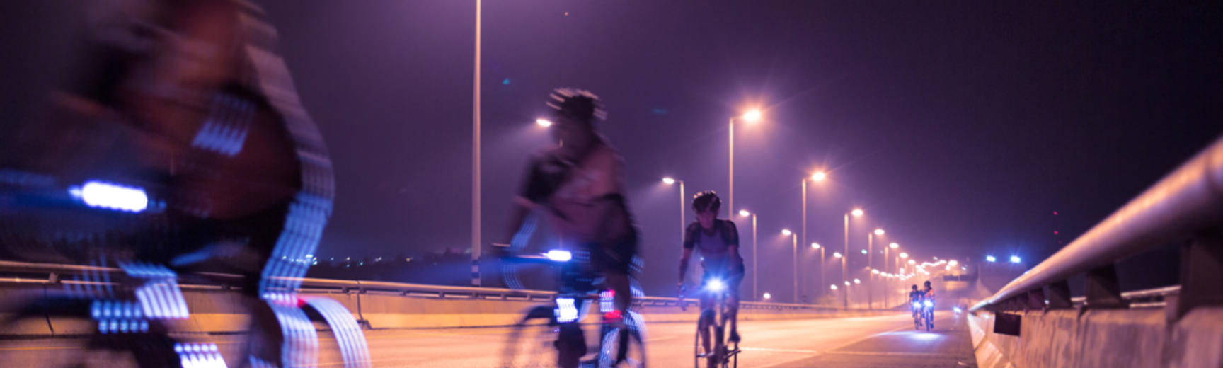 Image of cyclists riding at night with lights on bike
